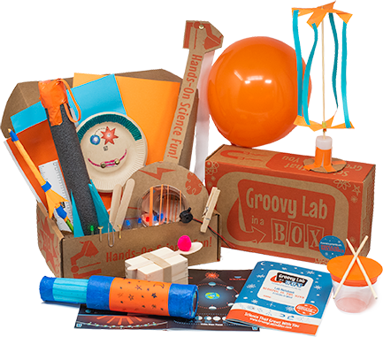 Photograph of an open Groovy Lab in a Box STEM box for kids showing a paper rocket, a foam rocket, a stitched light up face, a banjo, a balloon, a groovy twirler, drums, a telescope and a catapult along with supplies such as popsicle sticks, wire, LEDs, pom poms, papers and more.  There is an open lab notebook and a closed lab notebook in the foreground. All of the projects reflect science, technology, engineering and mathematics.